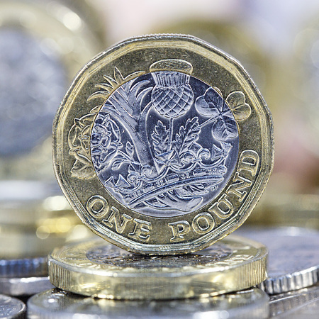 British Currency. One pound coin balancing on other coins with selective focus in a square format