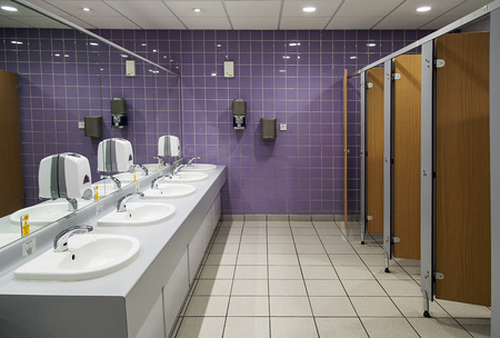 Public bathroom. Ladies restroom with cubicles and sinks and a purple tiled wall. Archivio Fotografico