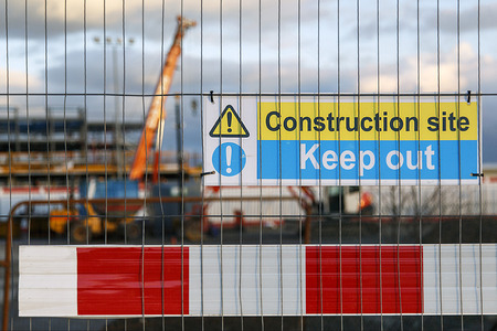 Construction site warning signs in yellow and blue instructing people to Keep Out.