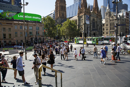 Melbourne, Australia: March 18, 2017: View of Federation Square and St Pauls Cathedral from the steps of Flinders Street Station. People are in a hurry crossing the street at the green light