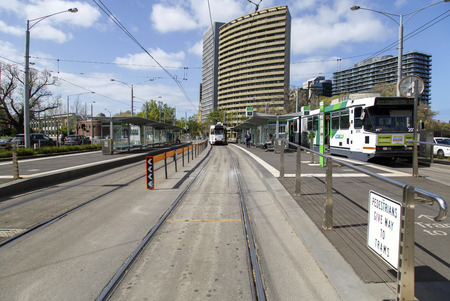 Melbourne, Australia: October 07, 2015: A tram is traveling along the tracks towards the camera in Melbourne. Pedestrians are walking on the pavement Sajtókép