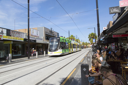 Melbourne, Australia: March 10, 2017: People eat and drink at the street cafes on Acland Street in St Kilda. A cable car passes by going into the city centre Sajtókép