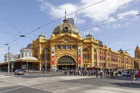 Melbourne, Australia: October 07, 2015: People cross the street in front of Flinders Street Station. It is the main railway station in Melbourne.