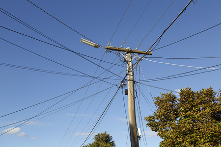 Telegraph pole with wires crossing over and a blue sky background