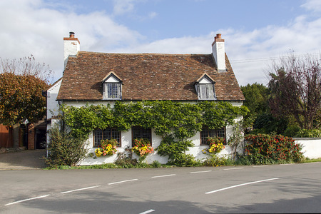 Stratford, UK: October 14, 2017: Beautiful, traditional old English cottage with red tiled roof, climbing clematis, and window boxes near Stratford upon Avon in England on a sunny day