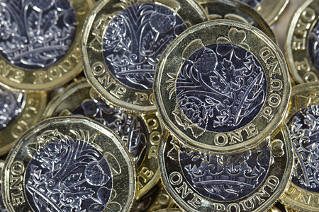 British Money - close up of a pile of British one pound coins in a horizontal format