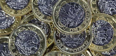 British Currency - close up of a pile of British one pound coins in a panoramic format Stock fotó