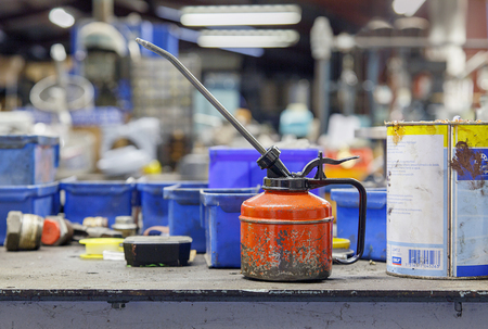 Birmingham, UK: December 27, 2017: Small oil can and plastic boxes on a workbench in a factory unit.