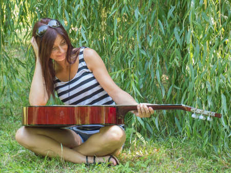 beautiful woman sitting on the green grass with a guitar photo