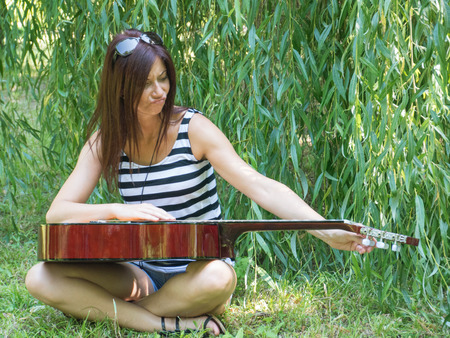 tough girl: tough girl grimace on the grass with guitar Stock Photo