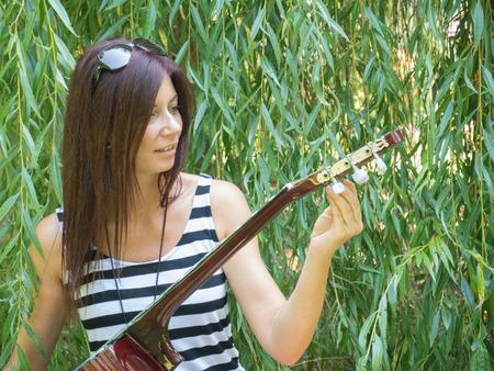 tune: beautiful red hair woman tune the guitart Stock Photo