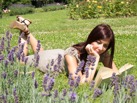 young red woman reading a book lying on the grass photo