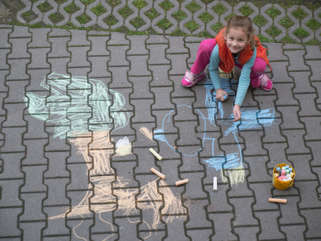 young girl drawing with crayons on the courtyard