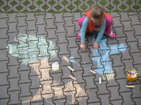young girl drawing with crayons on the backtyard