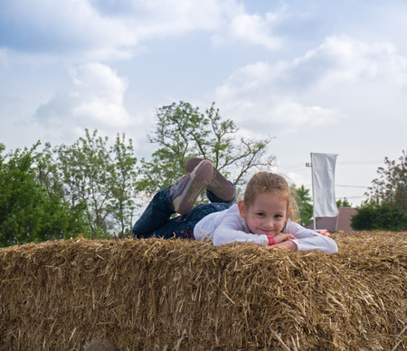 blonde girl lying down on brown hay at the vacation Stok Fotoğraf