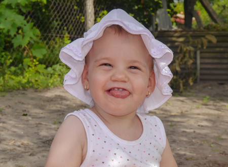 grimace: cute girl make a grimace in the garden Stock Photo