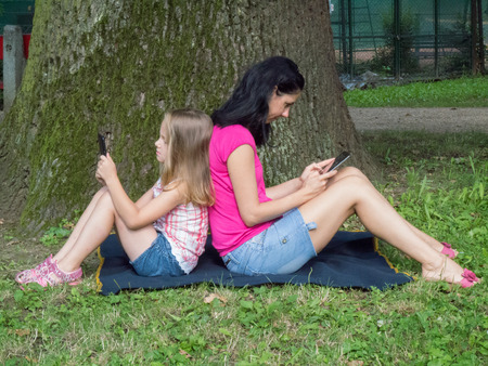 mother and daughter using tablet pc during a rest under the tree photo