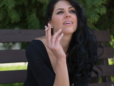 A pretty young dark haired woman smoking a cigarette while sitting on a park bench photo