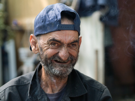 old and dirty homeless man laughing
