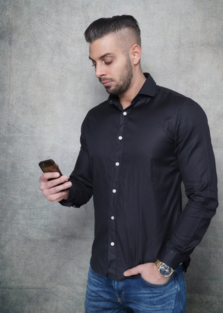 young bearded man in black shirt holding his phone in his hand in a photo studio