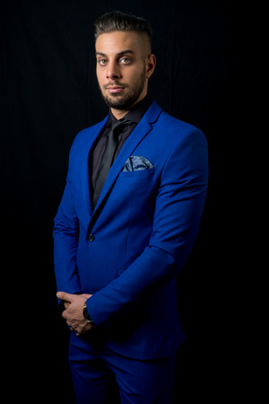 young bearded man in a blue suit standing in a photo studio with black background