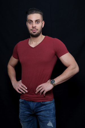 young man in a red t-shirt with a hand on his hands in a photo studio