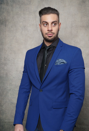 young bearded man in a blue suit standing in a photo studio