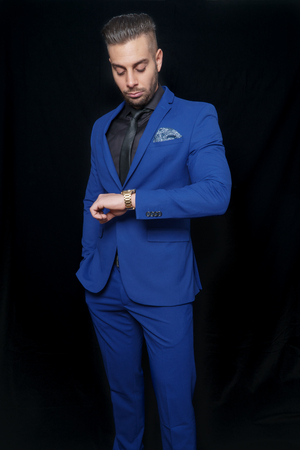 studio photography with young man in blue suit on black background