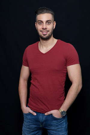 young man in a red shirt smiling in a photo studio with hands in a trouser bag Stok Fotoğraf