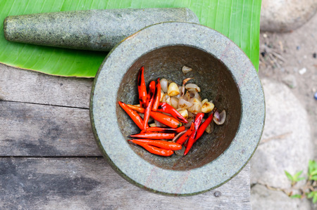 grill chilli garlic onion and pound in mortar stone photo