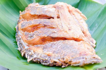 deep fried fish on green banana leaf photo