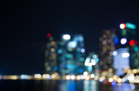 buildings city: Singapore building city night lights bokeh and reflect of marina bay blurred  background Stock Photo