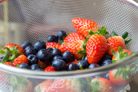 sieve: Fresh ripe red strawberries and blueberries in sieve
