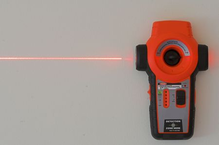 laser level hanging on wall with laser beam photo