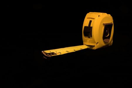 benchmarking: yellow retractable tape measure on black background