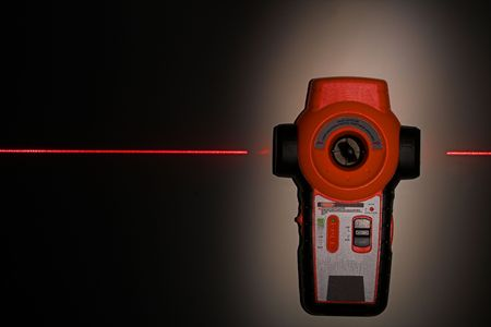 laser level hanging on wall with laser beam black background photo