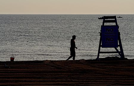 sihlouette: sihlouette of lonely man and lifeguard tower on beach