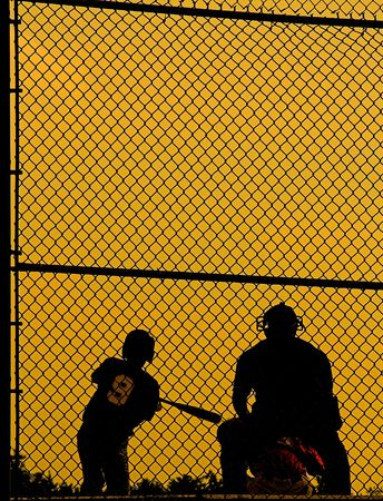 umpire, batter and catcher against sihlouetted against golden sky in evening. Stock Photo - 455069