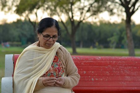 Shot of a senior retired Indian woman sitting in a park on a red bench peeling peanuts, and eating them. Concept - Retired life