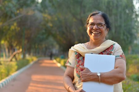 Portrait of a confident retired Senior Indian woman carrying a laptop in a park wearing off white salwar kamiz. Concept - Digital literacy in India for senior citizens