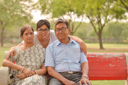 Family portrait of a young Indian woman with her mother and father posing in a park in New Delhi, India