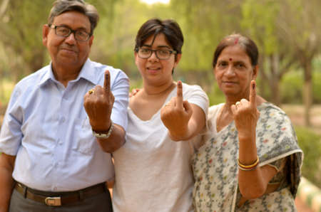 Happy Family portrait - Senior Retired parents and their daughter showing the inked finger after voting in Indian elections in an outdoor park. Celebrating world's largest democratic elections concept 版權商用圖片