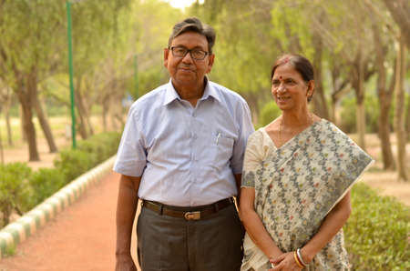 Happy looking retired senior Indian man and woman couple smiling and posing in a park outdoor setting in New Delhi, India. Concept love