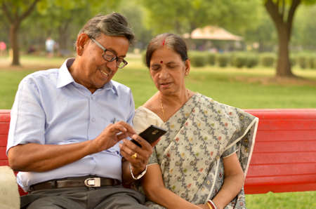 Portrait of senior couple sitting in park bench and looking at their smart phone and laughing in New Delhi, India with focus on the hands Archivio Fotografico