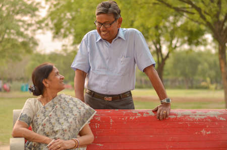 Happy looking retired senior Indian man and woman couple, sitting on a red bench, smiling and looking at each other in a park outdoor in New Delhi, India Stock Photo
