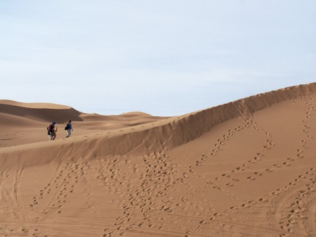 Walkers in the Sahara Desert, Morocco, with footprints on a dune photo