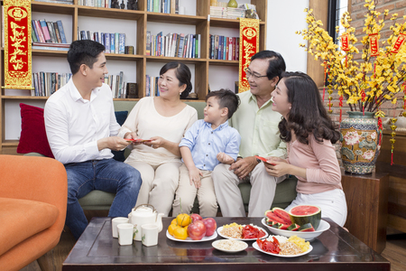 Asian family lunar new year at home with yellow apricot flower in the background Banco de Imagens