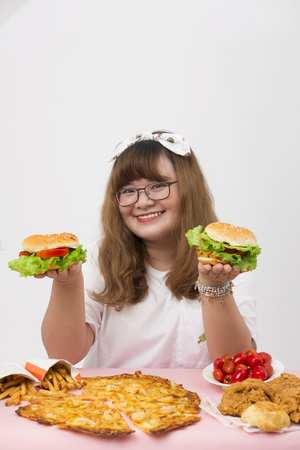 A lovely girl feeling happy and happy with fastfood on the table