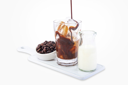 Ice coffee in a tall glass with cream poured over and coffee beans 免版税图像