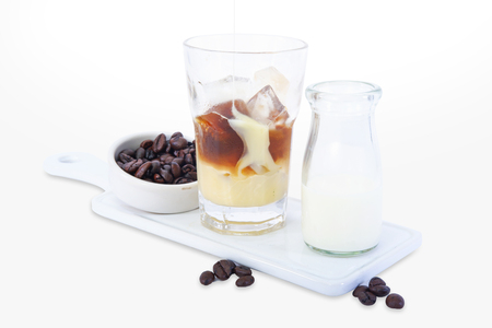 Ice coffee in a tall glass with cream poured over and coffee beans Reklamní fotografie